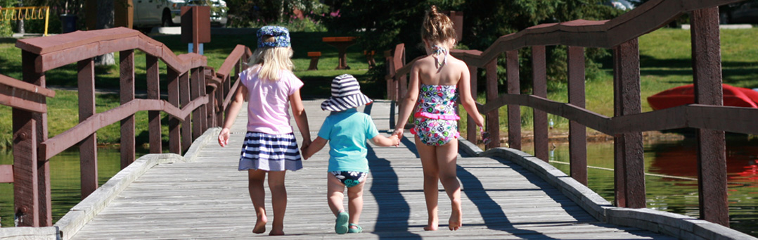 Three girls holding hands on the dock