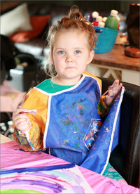 Young child painting with bright colours